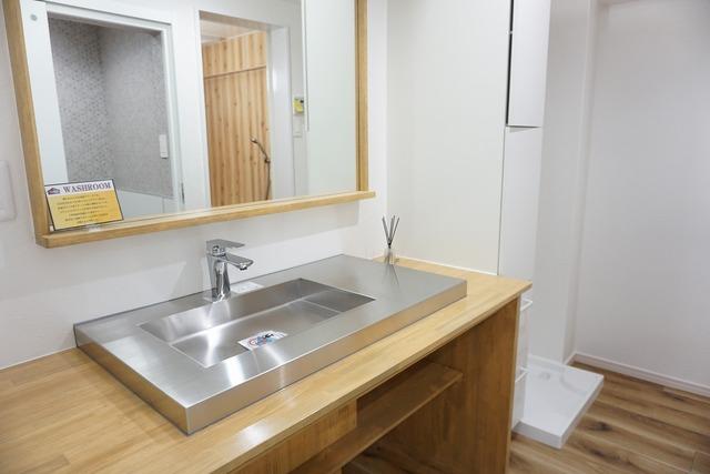 大きなミラーとステンレスの洗い場がポイントの洗面台です。収納場所もしっかり確保されています。