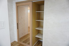 LDKの入口横に収納を設けています。キッチン横でもあるので、パントリーとしてもお使いいただけます。扉を開けた状態にすると、収納棚の扉になり面白い作りです。
