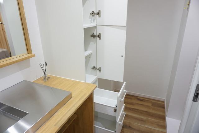 洗面台横に設けられた収納棚。散らかりがちなバスタオルや清掃用品、化粧品や予備のシャンプー等もきれいに整頓できますね。