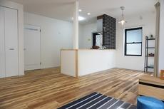リビングは広々とした設計で、家族が集い、寛ぐ暮らしの空間を演出しています。カウンターキッチンの黒いタイル部分もオシャレですね。