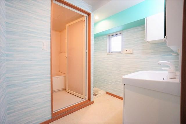 バスルームを含む洗面スペースは広々設計。水回りに合わせたクロスで明るく清潔感あふれる空間です。