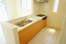 キッチンカウンターには、人造大理石を使用。美しいだけでなくお手入れも簡単。コンロ下の収納スペースはレールの付いたスライド式で取り出しがスムーズ。